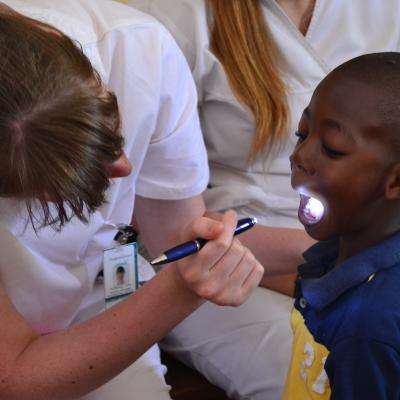 Female medical intern examines a young boy's mouth in a care centre during a medical internship in Jamaica.